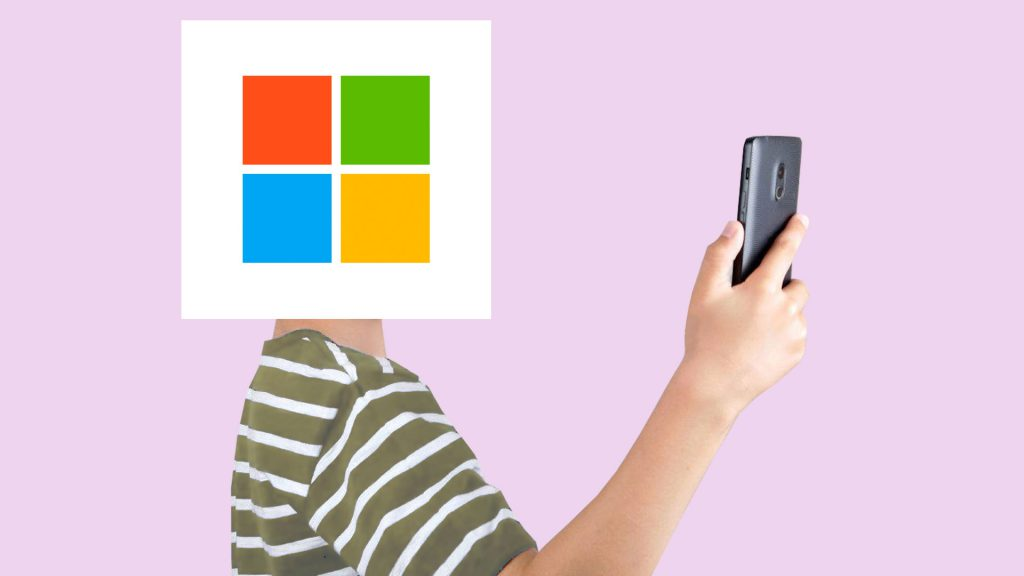A person with a Microsoft logo for a head holding a phne